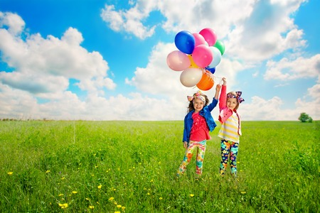 Cute happy children with balloons walking on spring field  Happiness, friendship, fashionable concept  Stock Photo