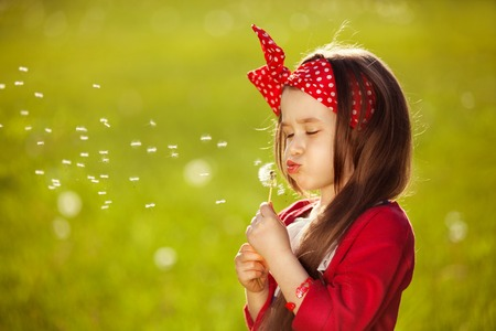 blowing dandelion: Beautiful little girl blowing dandelion  Happiness, fashionable concept  Stock Photo