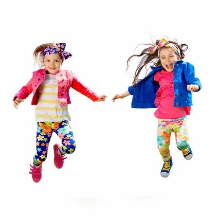 Roztomilý šťastné děti skákání izolované bílém pozadí. Štěstí, přátelství, módní pojem