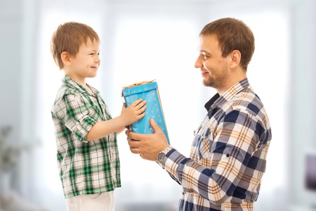 family fun day: Happy son gives his father gift