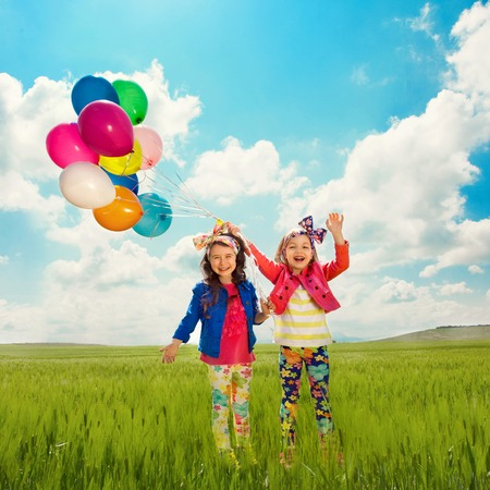 Cute happy children with balloons walking on summer field  Happiness, friendship, fashionable concept