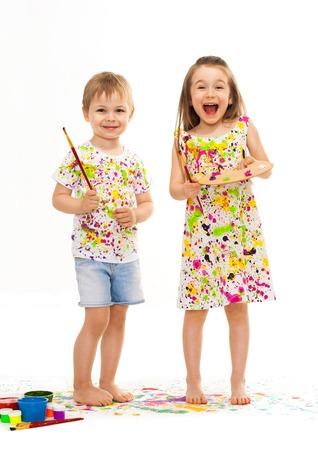 Roztomilý malý chlapec a dívka ledabyle hraje s barvami, izolovaných na bílém pozadí