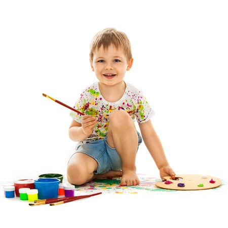 Smiling little boy painting, isolated on white background photo