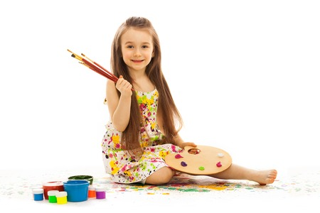 Smiling little girl painting, isolated on white background
