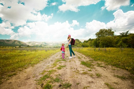 Mother and daughter walk on rural road through green field in summer  Happiness, lifestyle concept