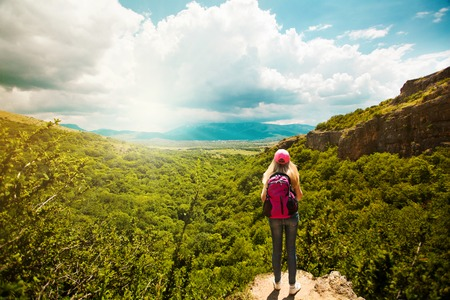 Young woman with backpack standing on cliff edge  Landscape composition  Happiness, lifestyle concept