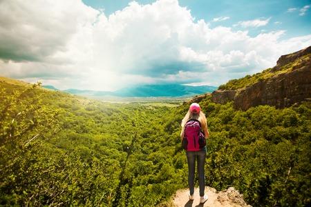 Mladá žena s batohem, stojící na okraji útesu, Krajina složení štěstí, koncept životního stylu