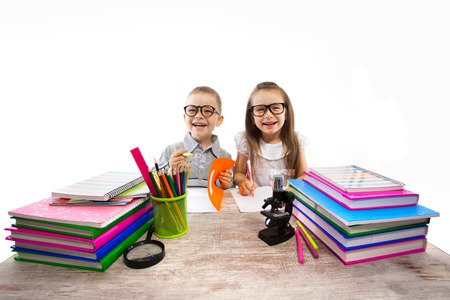Two smiling little kids at the table children doing homework, isolated on white background  School, education concept  Stock Photo