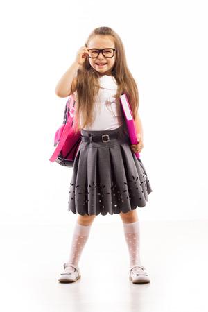 Školák s růžovým brašnu v brýlích knihu, izolované bílém pozadí. Vzdělání a školní koncepce