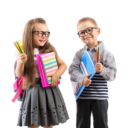 niño con mochila: Dos niños de la escuela sonriente con coloridos papelería, aisladas sobre fondo blanco. Escuela, concepto de la educación.