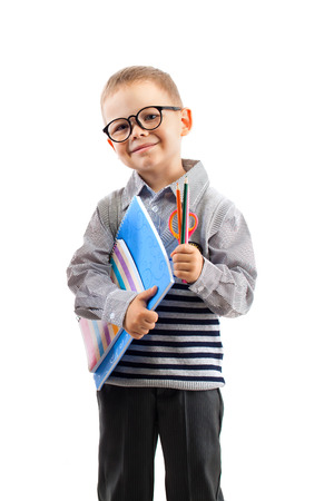 Schoolboy in glasses holding book,  isolated white background. Education and school concept  Zdjęcie Seryjne