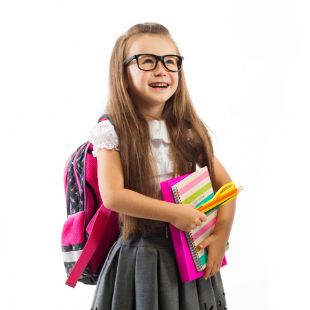Schoolgirl with pink satchel  in glasses holding book,  isolated white background. Education and school concept
