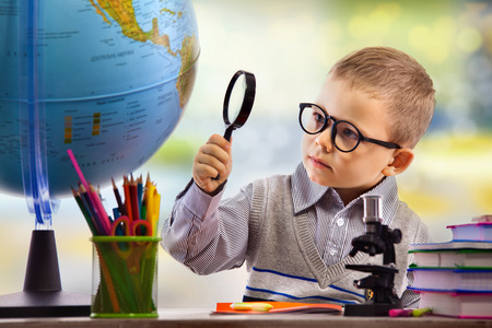 magnify glass: Boy looking through magnifying glass at globe, isolated on white background. School, education concept. Stock Photo
