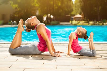 엄마와 야외에서 운동을하는 딸. 건강한 생활. 요가 스톡 콘텐츠