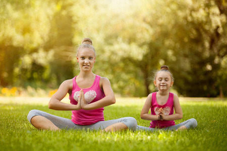 woman meditation: Sisters doing exercise outdoors. Healthy lifestyle. Yoga