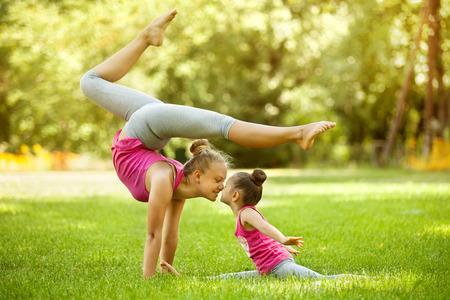 Matka a dcera dělá cvičení venku. Zdravý životní styl. Jóga