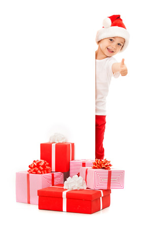 Little boy in Santa hat peeking from behind blank sign billboard and showing thumbs up. Isolated on white background. Space for Your Text. Sale, holidays, christmas, new year, x-mas concept. photo