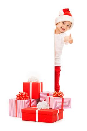 Malý chlapec v klobouku Santa pohlédl za za prázdný znak billboard a ukázal palce nahoru. Samostatný na bílém pozadí. Prostor pro text. Prodej, prázdniny, vánoční, nový rok, koncept xmas.