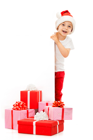 Happy little boy in Santa hat peeking from behind blank sign billboard. Isolated on white background. Space for Your Text. Sale, holidays, christmas, new year, x-mas concept. photo