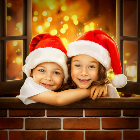 miracle tree: Happy kids in Santa hat  look out  window at Christmas time. With colorful lights from Christmas tree on background. Holidays, christmas, new year, x-mas concept. Stock Photo