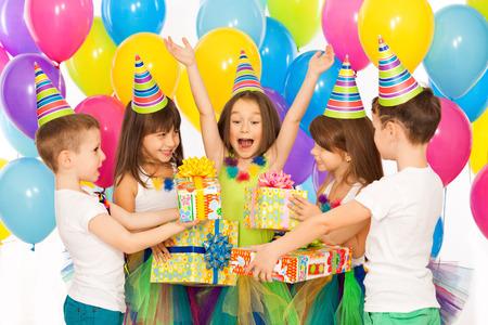 Blij klein kind meisje ontvangen giften bij verjaardagsfeestje. Vakantie, verjaardag concept.
