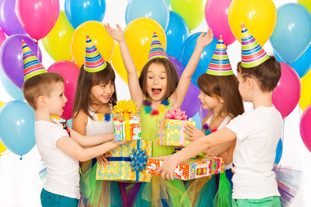 birthday party kids: Joyful little kid girl receiving gifts at birthday party. Holidays, birthday concept.
