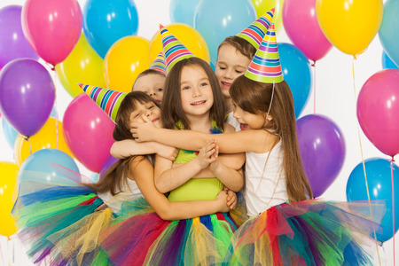 kids birthday party: Group of joyful little kids having fun at birthday party. Isolated on white background. Holidays, birthday concept. Stock Photo