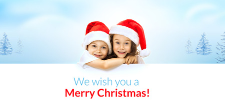 Happy little kids in Santa hat peeking from behind blank sign billboard. Isolated on white background. Space for Your Text. Sale, holidays, christmas, new year, x-mas concept.