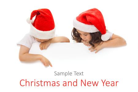 Šťastné malé děti v Santa klobouk pokukování zezadu prázdný znak billboard. Reklamní fotografie