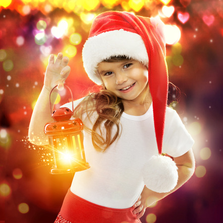 Happy little girl in Santa hat holding red Christmas lantern. With colorful lights on background. Holidays, christmas, new year, x-mas concept. Stock Photo