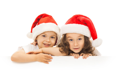 Happy little kids in Santa hat peeking from behind blank sign billboard. Isolated on white background. Space for Your Text. Sale, holidays, christmas, new year, x-mas concept. photo