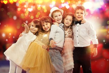 Skupina šťastné děti ve slavnostních šatech s barevnými světly na pozadí. Svátky, Vánoce, Nový rok, x-mas koncept. Reklamní fotografie