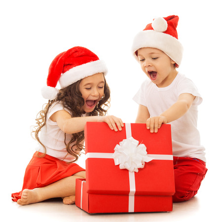 Happy kids in Santa hat opening a gift box. Isolated on white background.  With colorful lights from Christmas tree on background. Holidays, christmas, new year, x-mas concept.