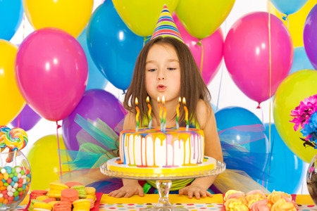Portrait of joyful little girl celebrating birthday party and blowing candles on cake. Holidays concept.