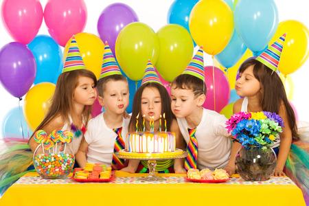 Groep van vrolijke kleine kinderen vieren verjaardag en blazen kaarsjes op de taart. Vakantie concept. Stockfoto
