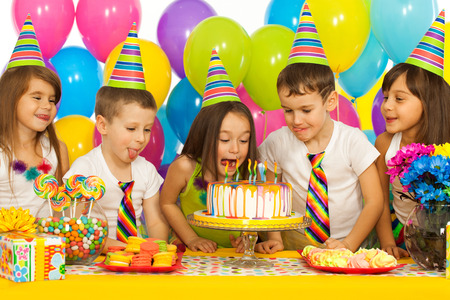 birthday party kids: Group of joyful little kids with cake at birthday party. Holidays concept. Stock Photo