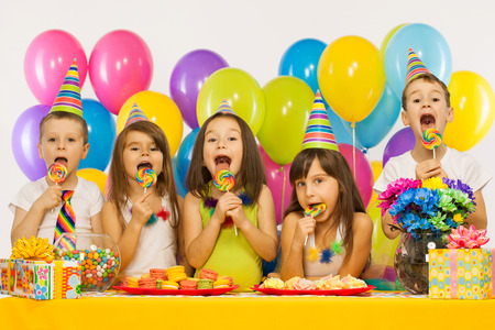 birthday party kids: Group of joyful little kids having fun at birthday party. Holidays concept. Stock Photo