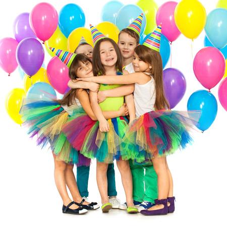 Skupina veselých malé děti baví na narozeninovou oslavu. Samostatný na bílém pozadí. Dovolená koncept. Reklamní fotografie