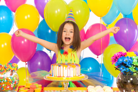 Portrait of joyful little girl with cake at birthday party . Holidays concept