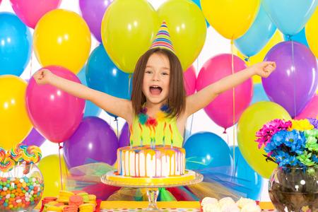 niÑos contentos: Retrato de la niña alegre con pastel en la fiesta de cumpleaños. Vacaciones concepto Foto de archivo