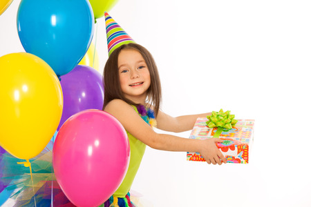 Happy little kid girl with gift box and colorful balloons on birthday party. Isolated on white background. olidays concept.