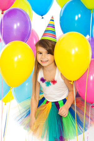 Happy little kid girl  with colorful balloons on birthday party. Holidays, birthday concept.