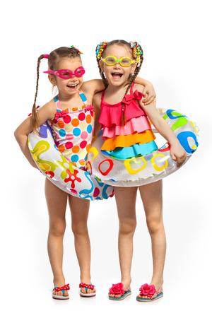 traje de bano: Felices los ni�os en traje de ba�o y anillos inflables. Aislado en el fondo blanco. Verano, de moda, el concepto de amistad. Foto de archivo