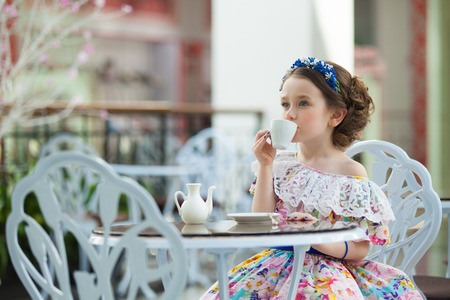 Portrait of elegant child girl in a floral dress drinking tea. Fashion kid, manners, fashionable concept.