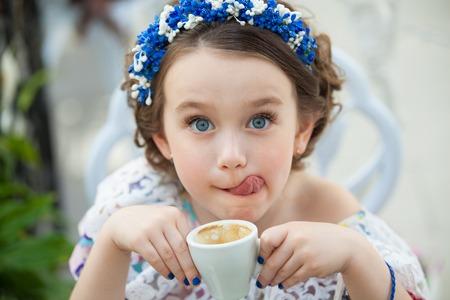 Portrét elegantní Dítě dívka v květinové šaty pití kávy. Fashion dítě, módní pojem.