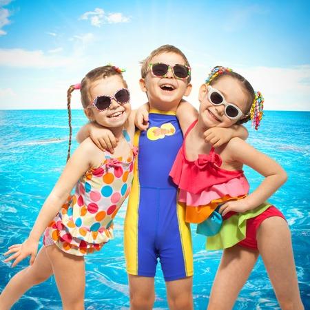 Счастливые дети в купальниках на море. Модный, дружба понятие.