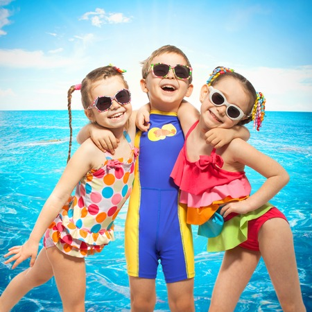 Happy kids in swimsuit at sea. Fashionable, friendship concept.