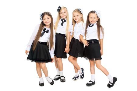 colegiala: Grupo de los sonrientes colegialas en uniforme escolar, aisladas sobre fondo blanco. La educación, la moda, el concepto de la amistad.
