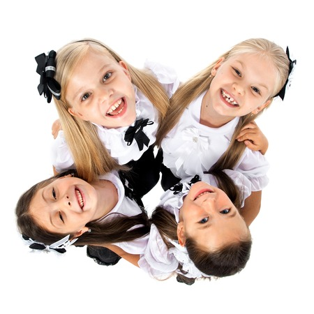 friendship: Group of smiling schoolgirls in school uniform, isolated on white background. Education, fashion, friendship concept.