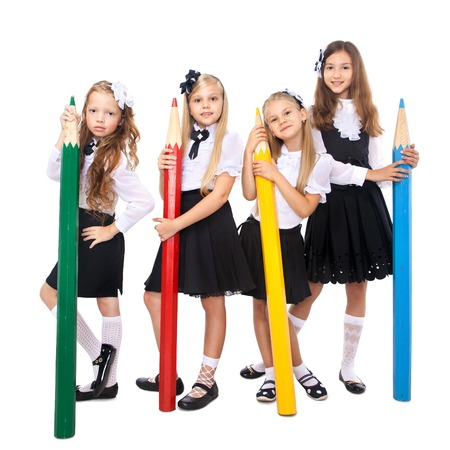 schoolgirl in uniform: Group of smiling schoolgirls with big colored pencils, isolated on white background. School, fashion, friendship concept. Stock Photo